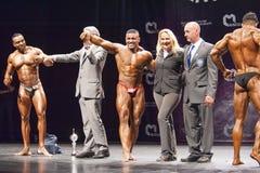 De bodybuilders vieren hun overwinning op stadium met ambtenaren Stock Foto