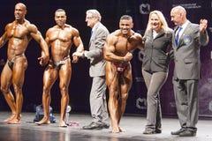 De bodybuilders vieren hun overwinning op stadium met ambtenaren Royalty-vrije Stock Afbeeldingen