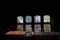 De boeddhistische lampen van het oliegebed in een donkere ruimte dichtbij venster, lichten branden, worden de groene bladeren gez Royalty-vrije Stock Afbeeldingen