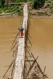 De boeddhistische monniken kruisen de Nam Khan-rivier op een bamboebrug, die beschermen tegen de zon met paraplu's, Luang Prabang stock fotografie