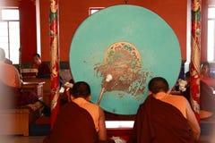 De boeddhistische monniken slaan trommels tijdens gebed bij Namdroling-Klooster op 27 Maart, 2015 in Bylakuppe, India Stock Foto's