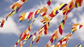 De boeddhistische vlaggen klappen onder de windvlagen van wind op de achtergrond van blauwe hemel stock footage