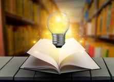 De boek gloeilamp is op de lijst Hout in het bibliotheekboek en gloeilampen Oud boek aan flarden op een houten lijstlezing door k stock foto