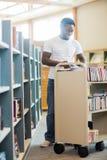 De Boeken die van bibliothecariswith trolley of in Bibliotheek werken Stock Fotografie