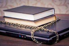 De boeken liggen op laptop die door een ketting wordt verbonden Boeken in plaats van computers Liefde aan read_ royalty-vrije stock foto's