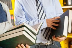 De Boeken van bibliothecarisand students holding in Universiteit Stock Afbeeldingen