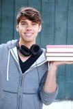De boeken van de jonge mensenholding buiten met hoofdtelefoons Stock Foto