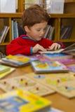 De boeken van de jongenslezing in een bibliotheek Stock Afbeeldingen