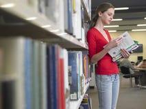 De Boeken van de meisjeslezing in Bibliotheek Stock Foto's