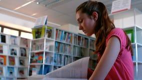 De boeken van de schoolmeisjelezing in bibliotheek stock video