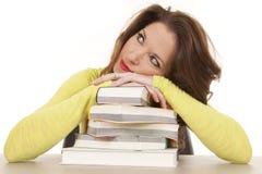 De boeken van de vrouwendagdroom leggen hoofd royalty-vrije stock afbeeldingen