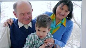 De boeken van de gepensioneerdelezing, kind met grootmoeder en grootvader het letten op beelden in dagboek stock footage