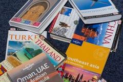 De boeken van het reisland op de vloer worden verspreid die naar volgende globale vakantie zoeken die Besluittijd stock foto's