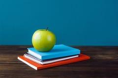 De boeken van de school met appel op bureau stock afbeeldingen
