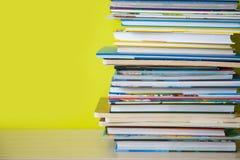 De boeken van vele kinderen worden gestapeld bovenop elkaar Groene bedelaars stock afbeeldingen
