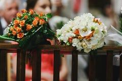 De boeketten van oranje en witte rozen liggen op de houten leuningen Royalty-vrije Stock Afbeeldingen
