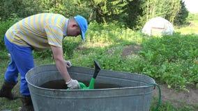 De boermens met gieter trekt water van watervat in tuin 4K stock footage