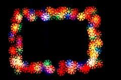 De Bokehsneeuwvlokken op sneeuwvlokken zwarte als achtergrond van verschillende kleuren worden geïsoleerd vormen een kader dat stock foto's