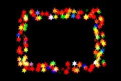 De Bokehsterren op sterren zwarte als achtergrond van verschillende kleuren worden geïsoleerd vormen een kader dat stock afbeeldingen