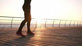 De bokser die zich vooraan de zonsopgang boven het overzees op het houten vloer doen bevinden oefent benen uit Duurzaamheid oplei stock videobeelden