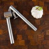 De bol en de pers van het knoflook op houten oppervlakte Royalty-vrije Stock Fotografie