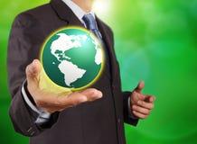 De bol van de aarde in zijn handen Stock Foto