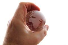 De bol van de glasaarde in menselijke hand Stock Afbeeldingen