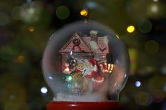 De bol van de glassneeuw met Santa Claus en lantaarn Kerstmisstuk speelgoed stock afbeeldingen