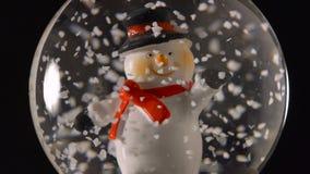 De bol van de de wintersneeuw met sneeuwman binnen op zwarte achtergrond stock footage