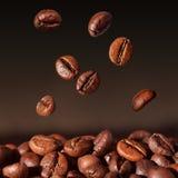 De bonen die van de koffie - close-up vallen Stock Afbeelding