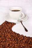De bonen die van de koffie een weg maken aan een witte kop Stock Foto's