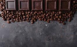 De bonen van de chocolade en van de koffie Donkere chocoladeachtergrond Een grote reep chocolade op grijze abstracte achtergrond Stock Afbeelding