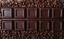 De bonen van de chocolade en van de koffie Donkere chocoladeachtergrond Een grote reep chocolade op grijze abstracte achtergrond Stock Foto's