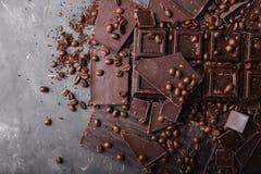 De bonen van de chocolade en van de koffie Donkere chocoladeachtergrond Een grote reep chocolade op grijze abstracte achtergrond Stock Foto