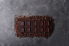 De bonen van de chocolade en van de koffie Donkere chocoladeachtergrond Een grote reep chocolade op grijze abstracte achtergrond Royalty-vrije Stock Afbeeldingen