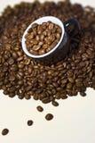 De bonen van de koffie in de zwarte kop. Sluit omhoog Stock Fotografie