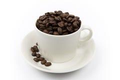 De bonen van de koffie in een kop stock foto's