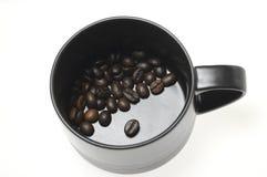 De bonen van de koffie in een kop Stock Afbeeldingen