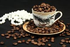 De bonen van de koffie in een kop en parels Royalty-vrije Stock Foto