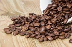 De Bonen van de koffie in een Kop op hout Stock Afbeeldingen
