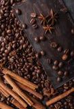 De bonen van de koffie en donkere chocolade Achtergrond met chocolade De bonen van de koffie Pijpjes kaneel en steranijsplant Stock Afbeeldingen