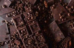 De bonen van de koffie en donkere chocolade Achtergrond met chocolade De bonen van de koffie Pijpjes kaneel en steranijsplant Royalty-vrije Stock Afbeelding