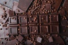 De bonen van de koffie en donkere chocolade Achtergrond met chocolade De bonen van de koffie Pijpjes kaneel en steranijsplant Royalty-vrije Stock Afbeeldingen