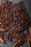 De bonen van de koffie en donkere chocolade Achtergrond met chocolade De bonen van de koffie Pijpjes kaneel en steranijsplant Stock Foto's