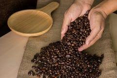 De bonen van de koffie in handen Stock Foto's