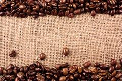 De bonen van de koffie op een juteachtergrond stock foto
