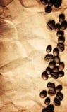De bonen van de koffie op een verfrommelde document textuurachtergrond stock afbeeldingen