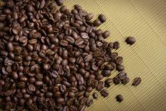 De bonen van de koffie op goud Stock Afbeelding