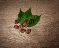 De bonen van de koffie op houten achtergrond Stock Afbeeldingen