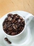 De bonen van de koffie in witte kopclose-up Stock Foto